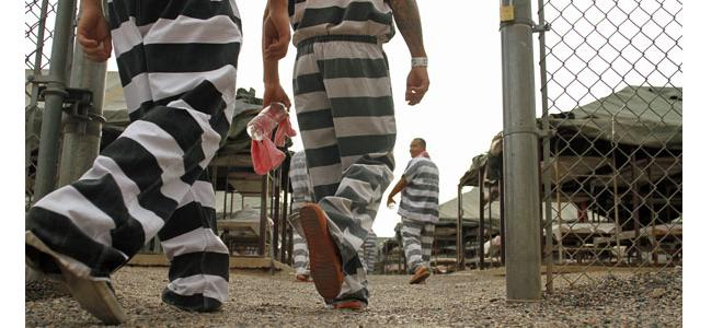 Inmates serving a jail sentence walk back to the yard at Maricopa County's Tent City jail in Phoenix