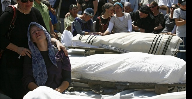 Mourners gather around the bodies during funeral in the West Bank Jewish settlement near Hebron